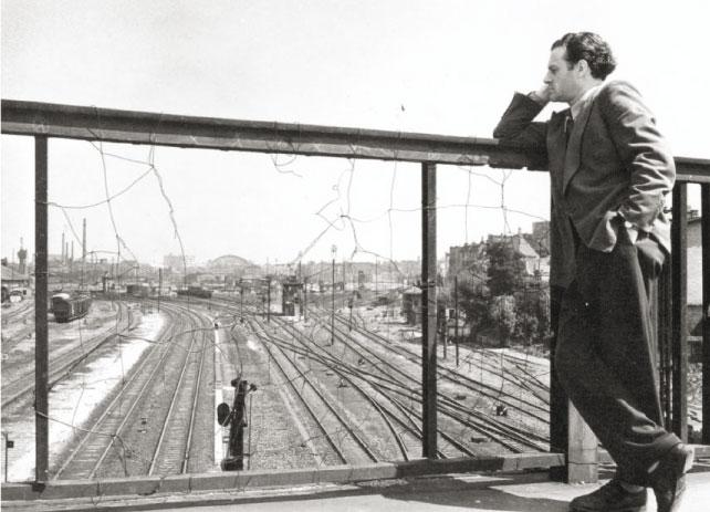 """1948 auf der Monumentenbrücke, am Horizont ist die Ruine des Anhalterpersonenbahnhofs zu sehen, heute sieht man dort das Tempodrom. In den Jahren vor 1945 war am nördlichen Geländer der Monumentenbrücke eine Sichtblende aus Holzbrettern installiert, um """"Spionen"""" den Ausblick zu verwehren."""